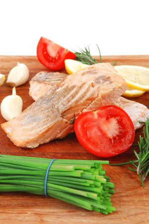 sea food : roasted pink salmon fillet with chinese onion, cherry tomatoes pieces, rosemary twigs and lemon on wooden board isolated over white background photo