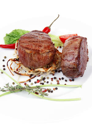 grilled beef fillet with thyme , red hot chili pepper and tomato on plate isolated over white background Banque d'images