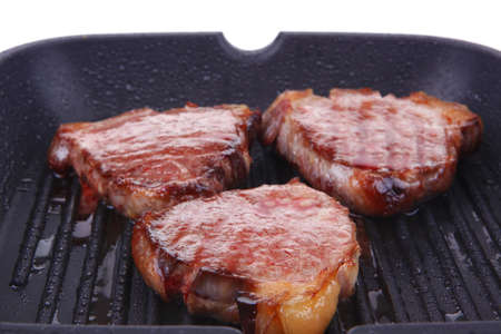 fresh grilled bloody beef steaks on black grill plate isolated on white background Stock Photo - 16026643