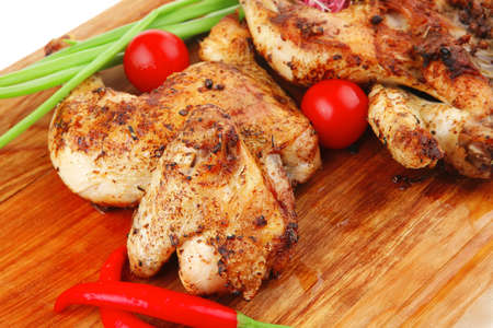 roast meat : chicken legs garnished with green sprouts and peppers on wooden plate isolated over white background