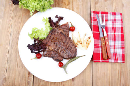 meat food : two grilled steak on green lettuce salad , with roast onion and red hot chili peppers , on dish over wooden table photo