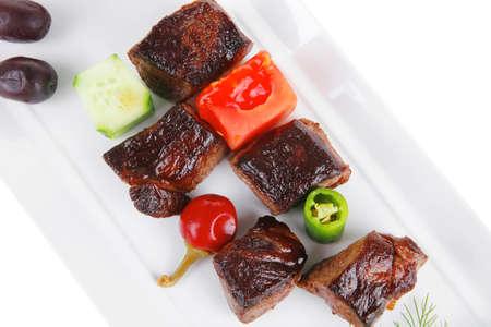 european food: alimentaria europea: a la carne de vacuno a la parrilla en plato de porcelana blanca aislados en fondo blanco con aceitunas y tomates