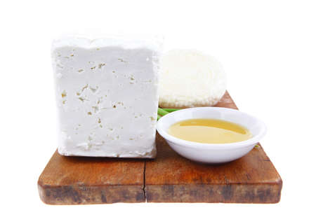diet food : greek feta white cheese served on small wooden plate with olive oil isolated over white background photo