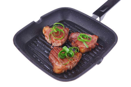 fresh grilled bloody beef steaks on black grill plate with green leaves isolated on white background photo