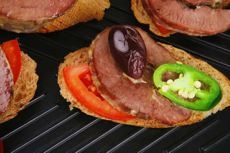 snakes on black grill plate : tartlets with sliced meat isolated over white background Stock Photo - 16025843