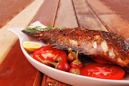 main course: whole fried seabass served on wood with lemons,tomatoes and peppers photo