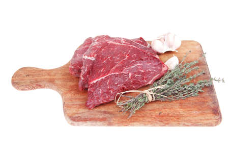 fresh raw beef meat fillet flesh with peppercorn and thyme ready to grill on wood figured old style board isolated over white background photo