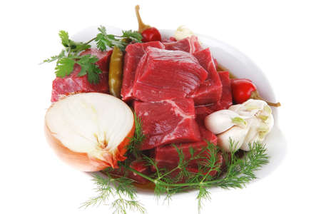 circular muscle: fresh uncooked beef meat slices over white bowls ready to prepare with red peppers and greenery isolated over white background