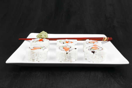 Maki Sushi - California Sushi Roll with Avocado, Cream Cheese and Raw Salmon inside. With wasabi . over black table photo