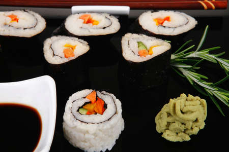 soysauce: Sushi Maki Roll with Vegetables and Salmon inside . on black plate with soysauce and wasabi . Japanese Cuisine