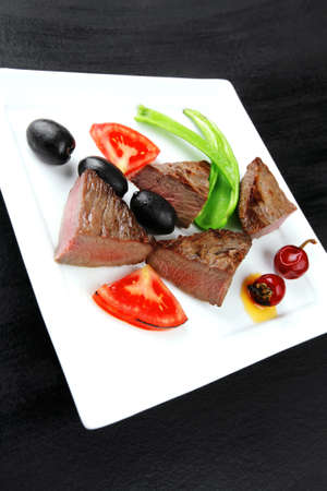 meat savory : grilled beef fillet mignon served on white plate over black wooden table with chili pepper and tomatoes Stock Photo - 16148813