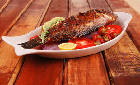 main course: whole fried seabass served on wood with lemons,tomatoes and peppers Stock Photo - 16149681