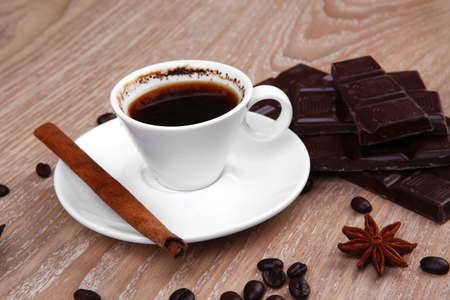 sweet hot drink : black coffee in small white cup with beans on a wooden table with stripes of dark chocolate and cinnamon sticks photo