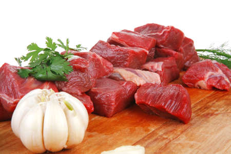 fresh raw beef meat slices over a wooden board with dill , green  and red hot peppers isolated over white backkground Standard-Bild