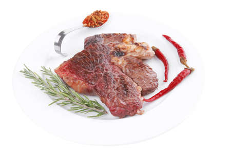 meat food : roast beef steak served on white plate with red pepper , spices , and rosemary isolated over white background photo