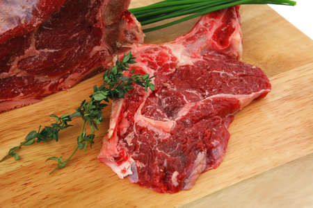 raw meat : boned fresh ribs served with thyme and green chives on wooden board isolated over white background Stock Photo - 16315326
