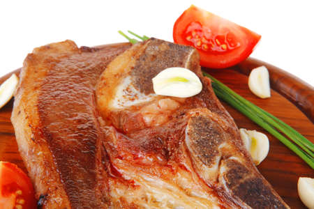 fresh hot roasted lamb meat fillet ready on red wooden plate with tomatoes, green pepper , and garlic isolated over white background Stock Photo - 16315301