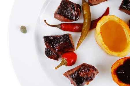 european food: europeo de alimentos: goulash carne a la parrilla en plato blanco con aj� picante, alcaparras y salsas