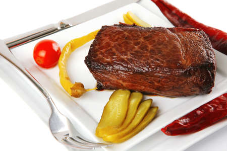 beef chunk with peppers on white plate photo