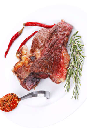 meat food : grilled beef steak served on white plate with red thin chili pepper and spices isolated over white background photo