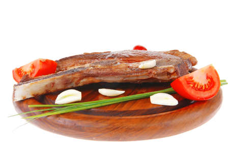 fresh hot roasted lamb meat fillet ready on red wooden plate with tomatoes, green pepper , and garlic isolated over white background Stock Photo - 16498383