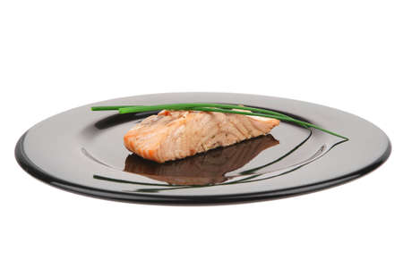 entree: savory sea fish entree : roasted salmon fillet with green onion, on black dish isolated over white background Stock Photo
