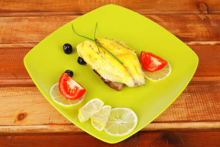 roast fish fillet with tomatoes,chives and bread on plate over wood photo