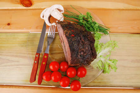 hot beef on transparent plate over wood table   photo