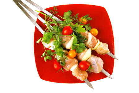 raw chicken kebabs served with on red plate photo