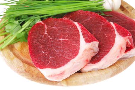 rind: rohes Fleisch: frisches Rindfleisch Schweinefilet St�cke mit Knoblauch und gr�ne Zeug auf Holz isoliert auf wei�em Hintergrund