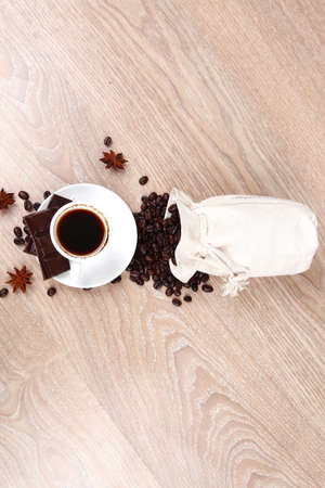 sweet hot food: black coffee with dark chocolate and coffee beans in bag on wooden table photo