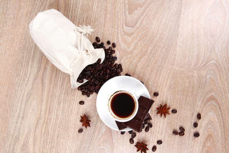 sweet hot food: black coffee with dark chocolate and coffee beans in bag on wooden table Stock Photo - 16572486