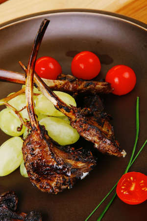 ribs on dish over wooden table with cherry photo