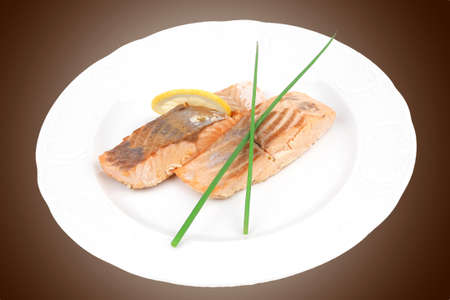 healthy fish cuisine : baked pink salmon steaks with green onion and lemon on white dish isolated over white background photo