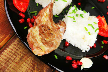 baby rice: meat portion: barbecued ribs served with rice and tomatoes on black over wood