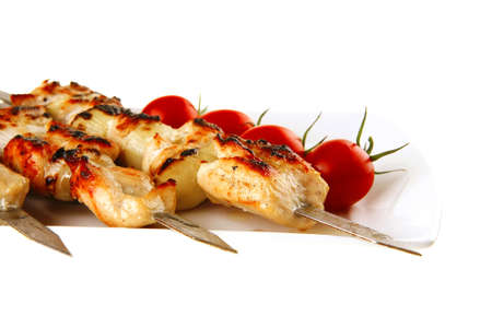 chicken shish kebab on white platter with vegetables photo