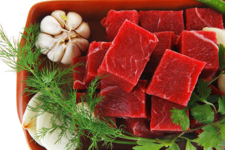 slices of raw fresh beef meat fillet in a ceramic dish with onions and peppers isolated over white background photo
