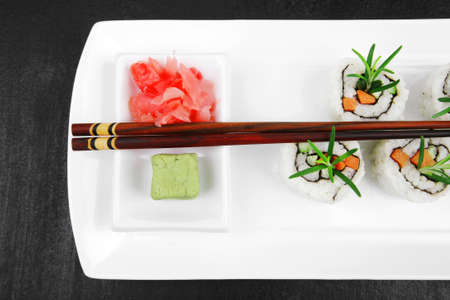 Maki Sushi - California Roll made of Smoked salmon, Cream Cheese and Deep Fried Vegetables inside. With wasabi and ginger. on black table Stock Photo - 16739002