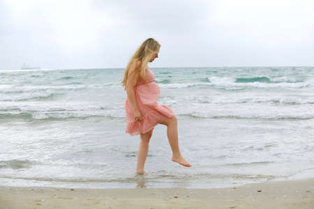 Portrait of a young beautiful blond pregnant woman at beach   on sea background  photo