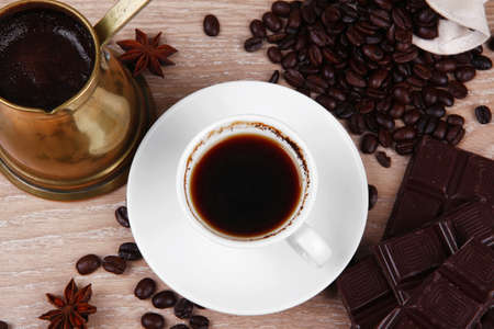 cezve: sweet hot drink   black coffee with beans in a white bag on a wooden table with stripes of dark chocolate and copper cezve