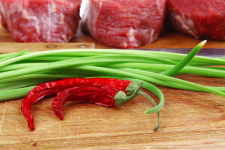 fresh meat : raw beef fillet on wooden board with thyme and red hot dry pepper ready to prepare . isolated over white background Stock Photo - 16738394