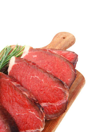 fresh raw red meat with thyme and chives on wooden plate isolated on white background photo