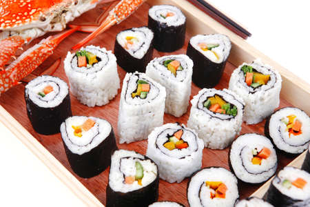 California Roll with Avocado and Salmon, Cream Cheese and Raw Salmon inside. on wooden plate with live crab  . isolated over white background . Maki Sushi and Sashimi photo