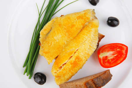 roasted fish fillet with tomatoes,chives and bread on plate over white plate photo