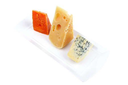 gruyere: fresh aged french cheese parmesan roquefort and gruyere chops on white plate with isolated over white background