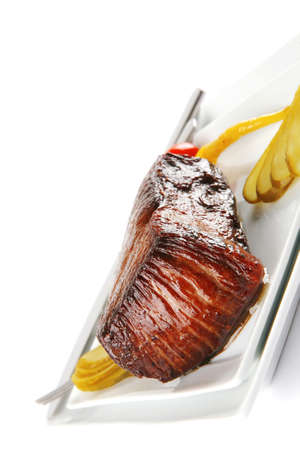 meat chunk on white with kitchenware and peppers photo