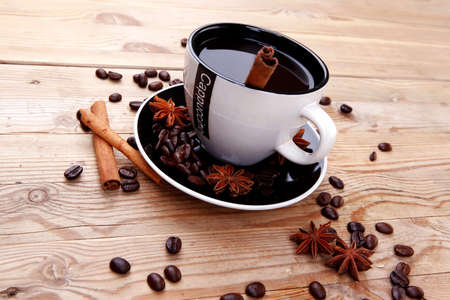 sweet dessert : black coffee and chocolate cake with cinnamon , coffee beans, and anise star on wooden table photo