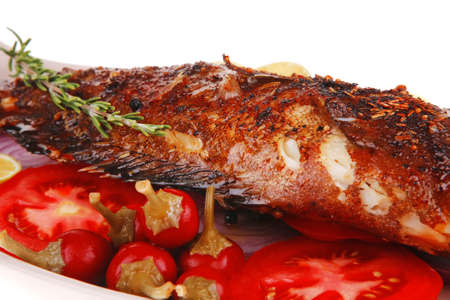 whole fried bass on plate, served with lemons and tomatoes Stock Photo - 16989961
