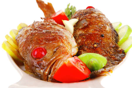 savory on plate: two fried fish served with tomatoes lemon and rosemary photo