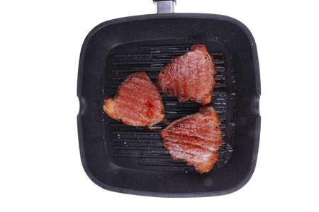 fresh grilled bloody beef steaks on black grill plate isolated on white background photo